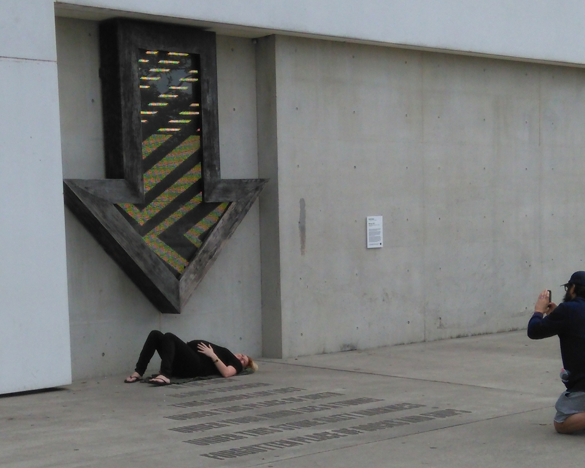 A woman lies unable to move after coming into contact with the pulsating LED arrow in Brook Andrew's Warrang, 2012 outside the Museum of Contemporary Art Australia. A man photographs her with his smartphone.